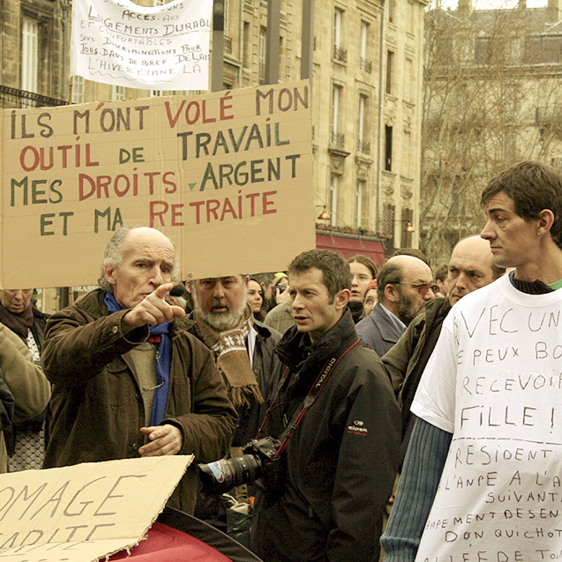 <In the crowd of a demonstration, under slogans for the homeless and next to a press photographer, a man is pointing his finger straight ahead