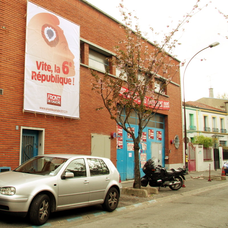 <A red brick building with a large poster for the 6th republic, the headquarters of the Left Front movement campaign during 2012 in the district of Les Lilas in Paris