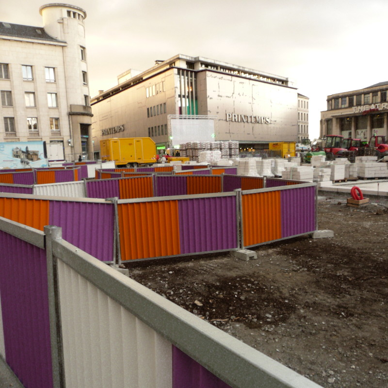 Collection of orange and purple construction barriers, on the large renovation site in the town centre of Poitiers, in front of the former Printemps department store and its abandoned facade