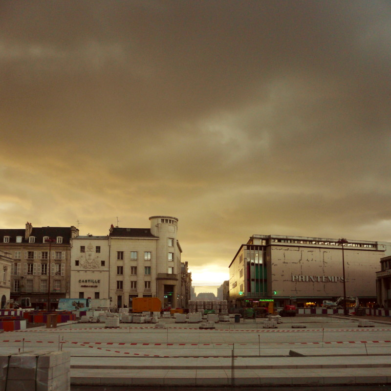 <Beginning of the paving of the town hall square in Poitiers, without any longer trace of plant life, under a sky filled with anthracite clouds.