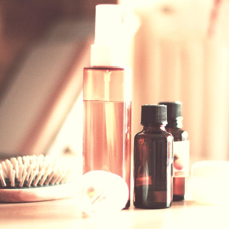 Une brosse à picots de bois clair, des flacons ambrés et un vapo d'eau dans un décor couleur abricot flouté