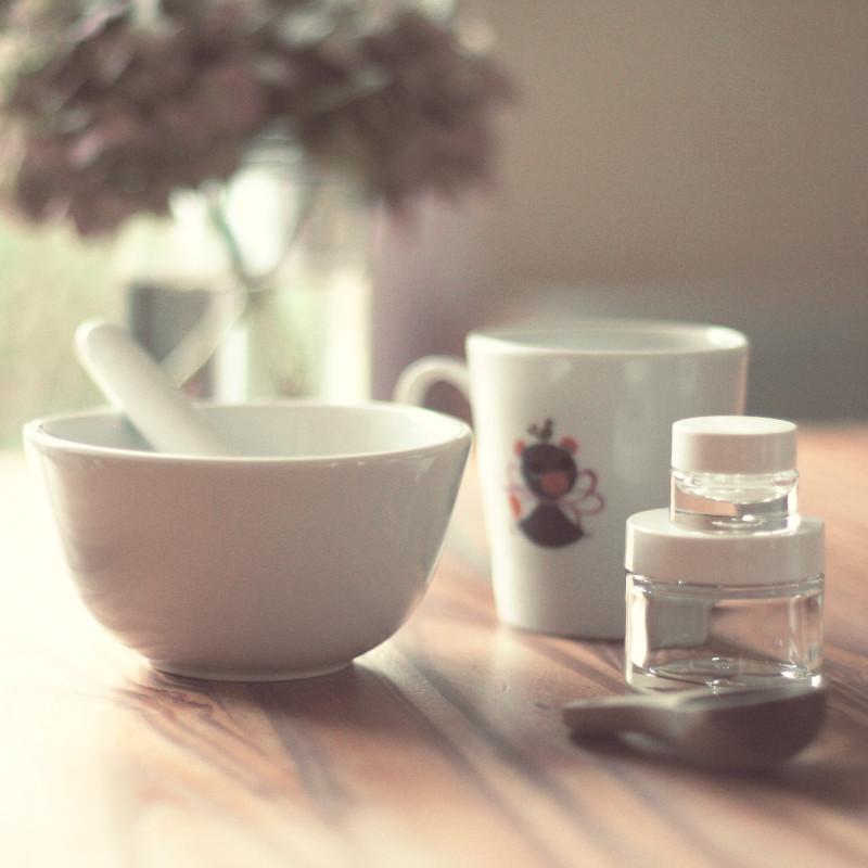 Un bol en céramique blanche et son pilon, deux pots en verre à couvercle blanc de différentes tailles, un mug blanc décoré d'un canard violet, une petite cuillère en bois foncé