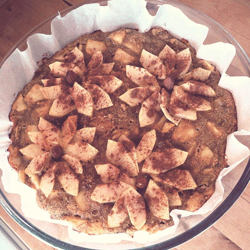 Vus du dessus un gâteau dans un papier de cuisson et un moule à manqué en verre décoré de quatre amandes autour desquelles des quartiers de pomme sont disposés en fleurs