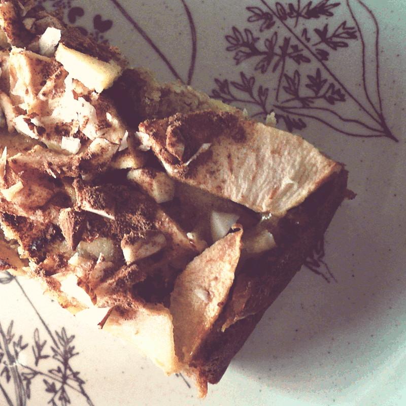 Gros plan sur le mélange dessus le gâteau rectangulaire où la poudre de cannelle s'est fondue avec les pommes parsemées de gros morceaux d'amandes