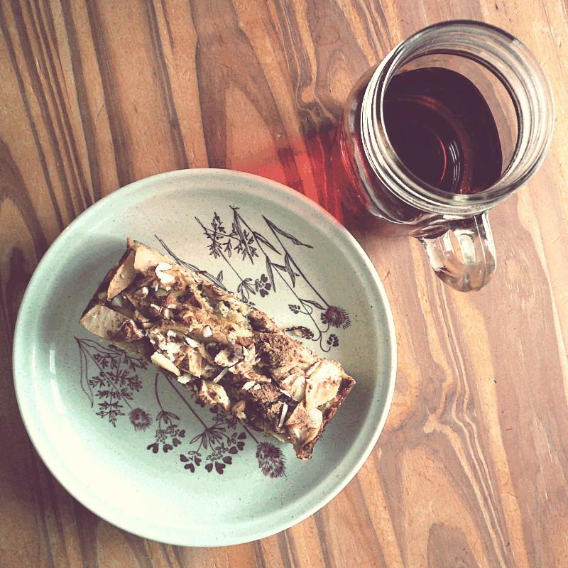 La même assiette vue plus largement posée à côté d'un grand mug en verre contenant une infusion d'hibiscus
