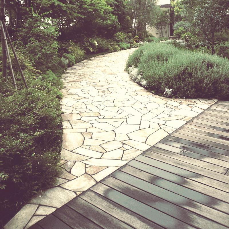 Une allée courbée et dallée dans un jardin touffu de verdure qui semble déboucher sur une terrasse en bois