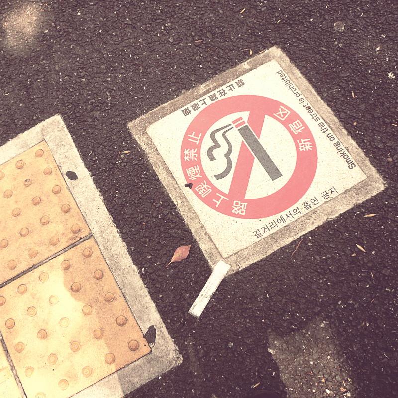 Sur l'asphalte gris pétrole de la route à côté d'une dalle pododactile jaune est incrusté le pictogramme de l'interdiction de la cigarette en rouge et blanc