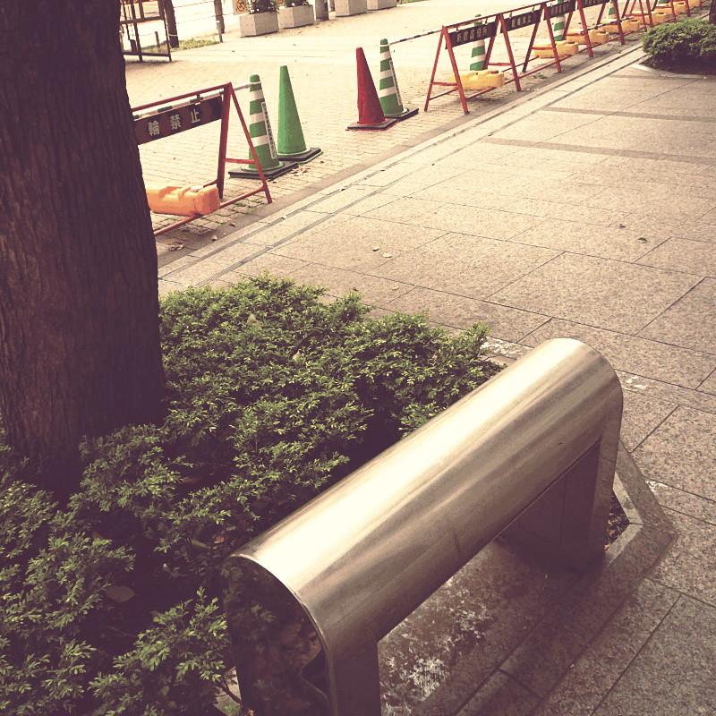 Sur un large trottoir dallé de granit et au pied d'un arbre entouré de petits buissons, un banc en métal dont l'assise est complètement arrondie