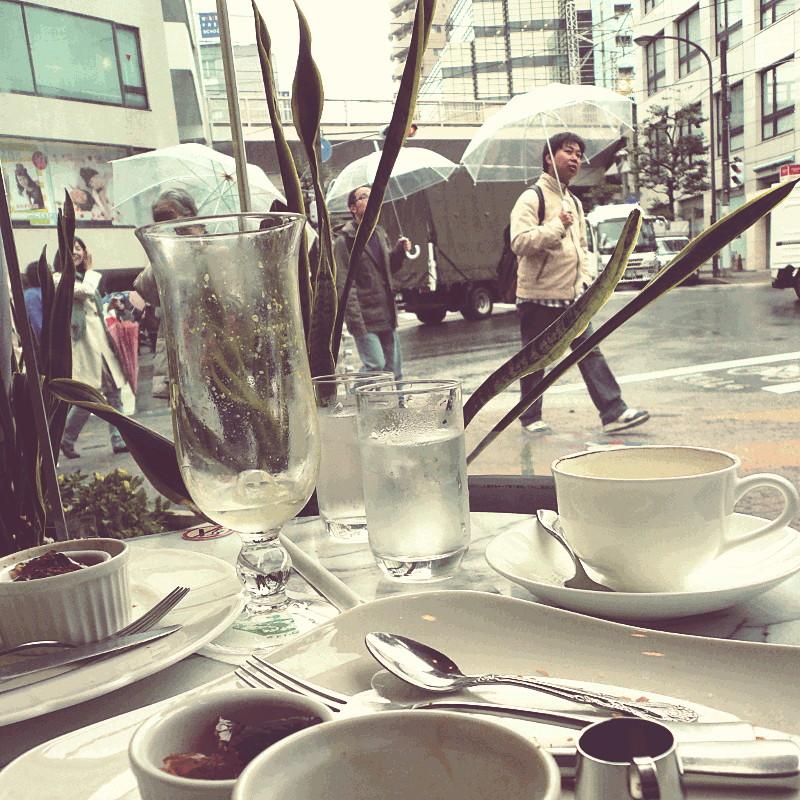 Au premier plan la vaisselle et les restes d'une pause gourmande dans un salon de thé face à une baie vitrée donnant sur le va-et-vient des passants équipés de parapluie en plastique transparent