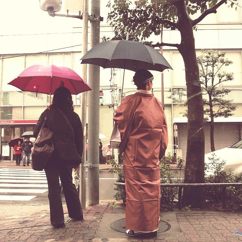 À un carrefour entre poteaux, fils éléctriques et arbres de villes attendent sous leur parapluie noir ou fushia deux femmes brunes vues de dos, dont une est habillée d'un kimono couleur caramel encore marqué des plis de la boîte où il devait être soigneusement rangé
