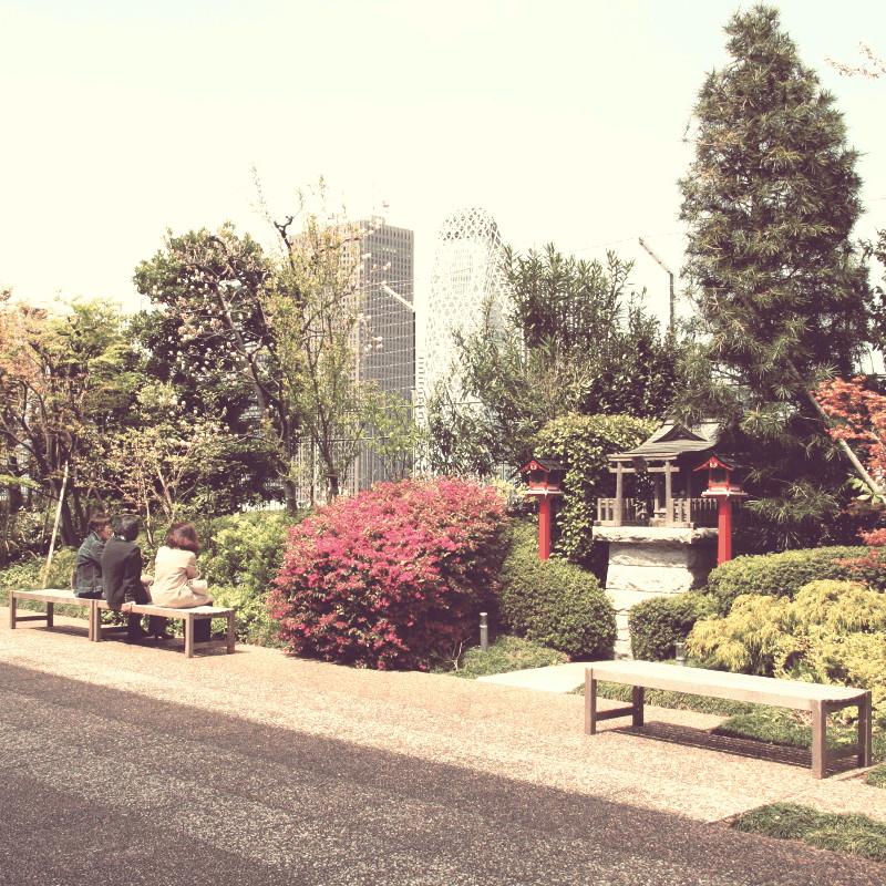 Une large terrasse dallée bordée de plantes et arbustes savamment implantés pour jouer avec les contrastes de leur couleur et qui entourent un tout petit sanctuaire Shinto devant lequel sont disposés quelques bancs dont l'un d'eux est occupé par trois femmes qui discutent en profitant de la vue sur la Mode Gakuen Cocoon Tower