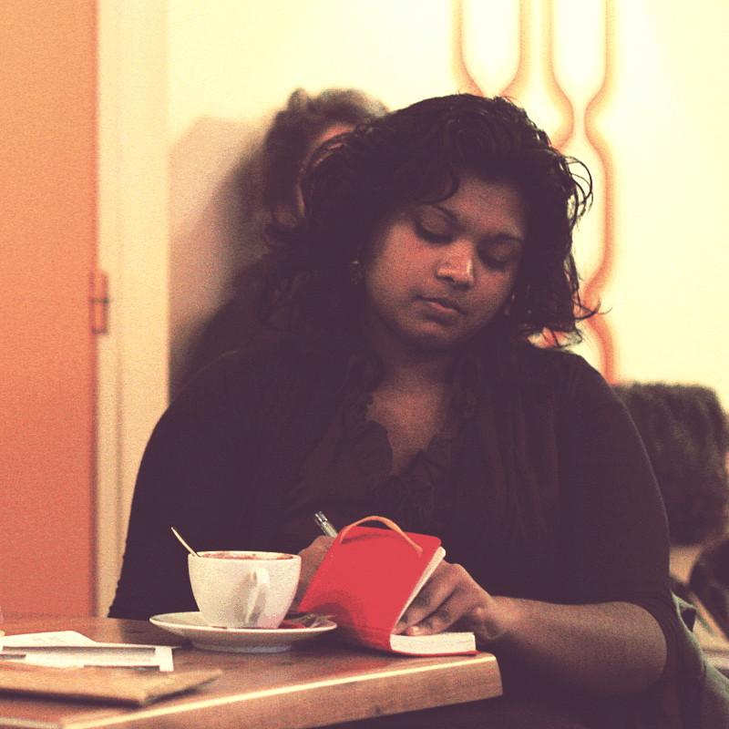 Dans un café une jeune femme brune à la peau mate et vêtue de couleur chocolat écrit sur un carnet rouge
