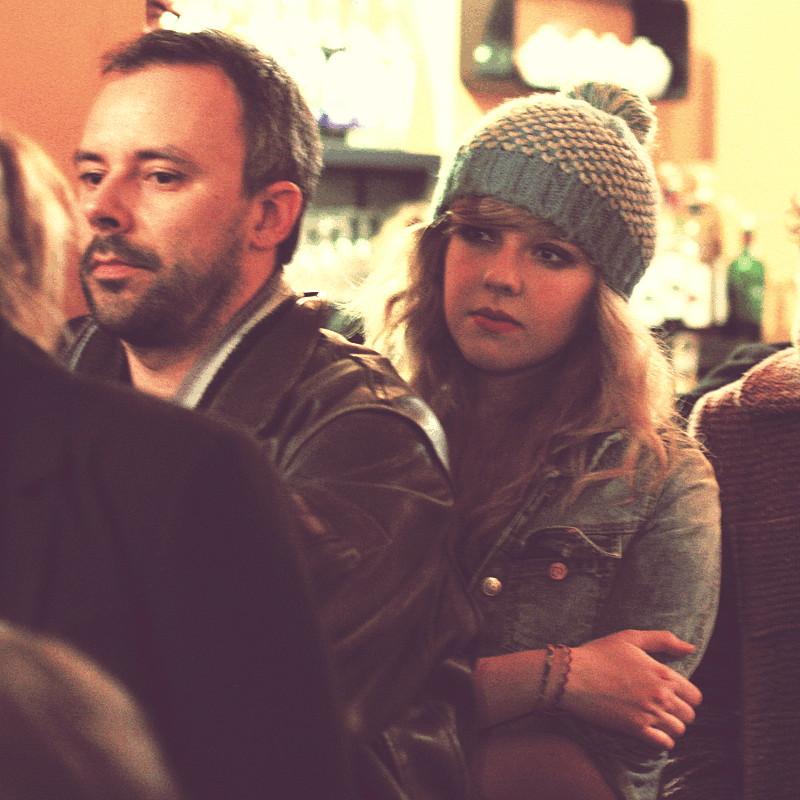 Un homme au blouson de cuir et une jeune femme blonde juste derrière lui coiffée d'un bonnet assorti à sa veste en jean, sont tous deux dans un café à l'occasion de l'écoute publique d'un meeting de campagne des présidentielles