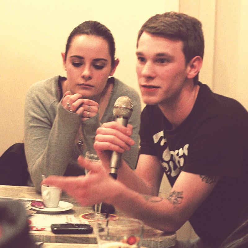 À une des tables assis devant une tasse de café ou un verre de bière, une jeune femme et un jeune homme qui tient un micro et a pris la parole