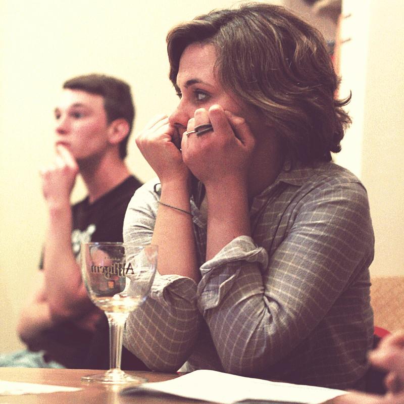 Une jeune femme assise devant son verre de bière vide tient son visage dans ses poings en écoutant la conférence, derrière elle et flou le jeune homme au micro de tout à l'heure qui porte son doigt à ses lèvres et semble être concentré